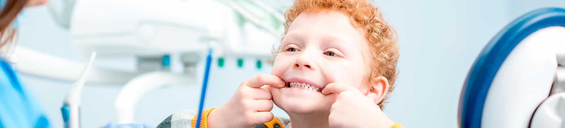 Little red-haired boy in a dentist treatment room showing his teeth.