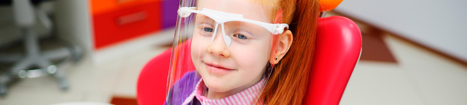 Relaxed little red-haired girl wearing a face shield in a dental chair.