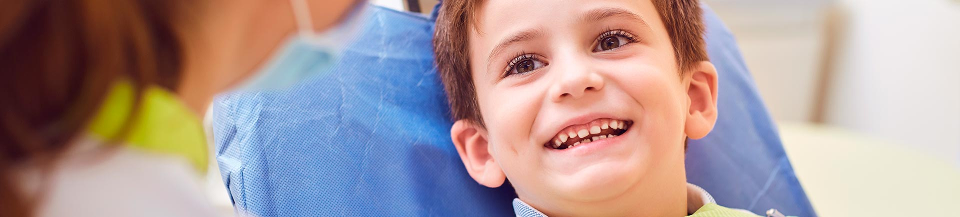 Relaxed joyful little boy in a dental chair during a dental appointment.