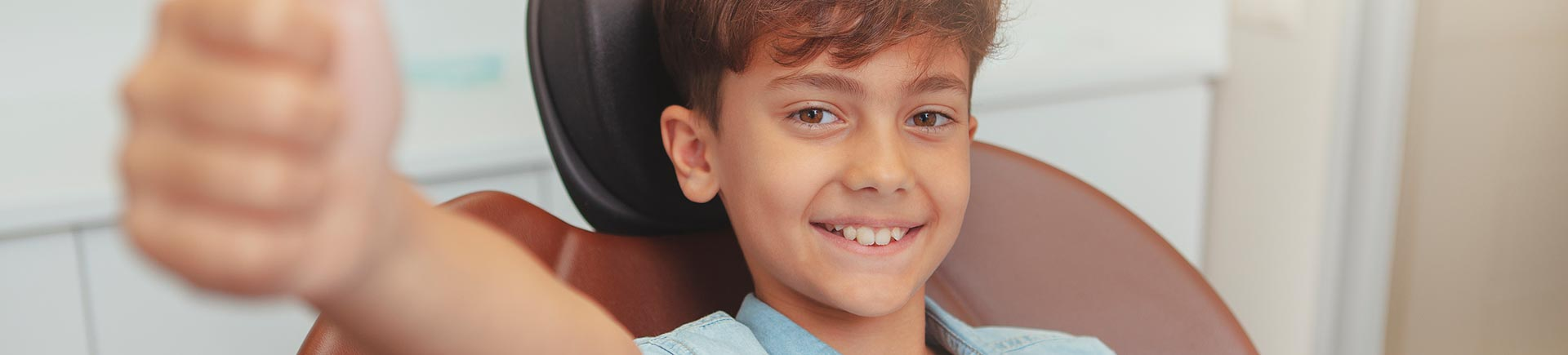 Cheerful young boy smiling in a dental chair showing his thumb up.