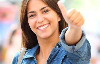 Happy teenage girl showing her thumb up.